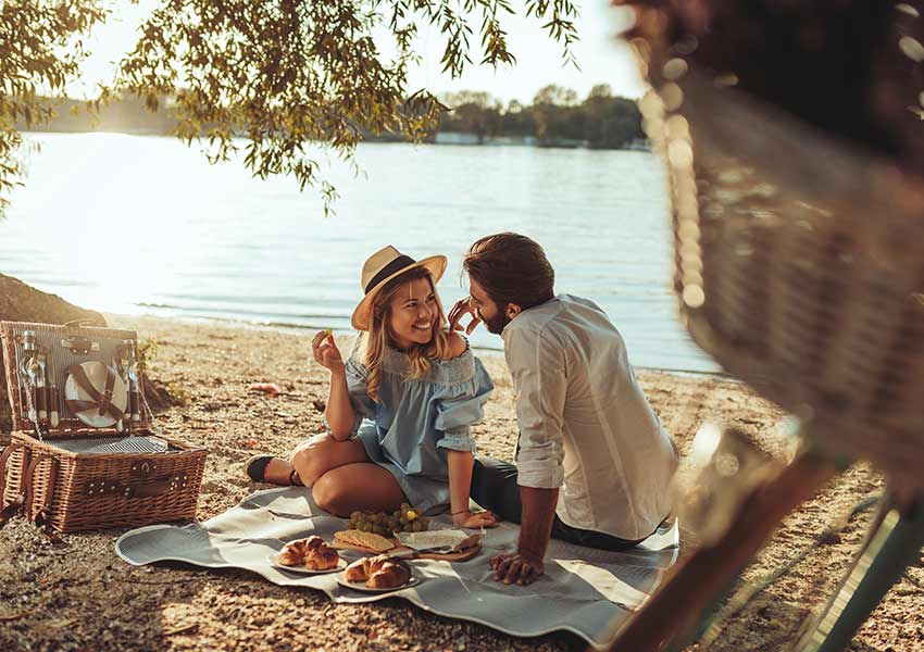 Newly married couple enjoying a picnic on their honeymoon