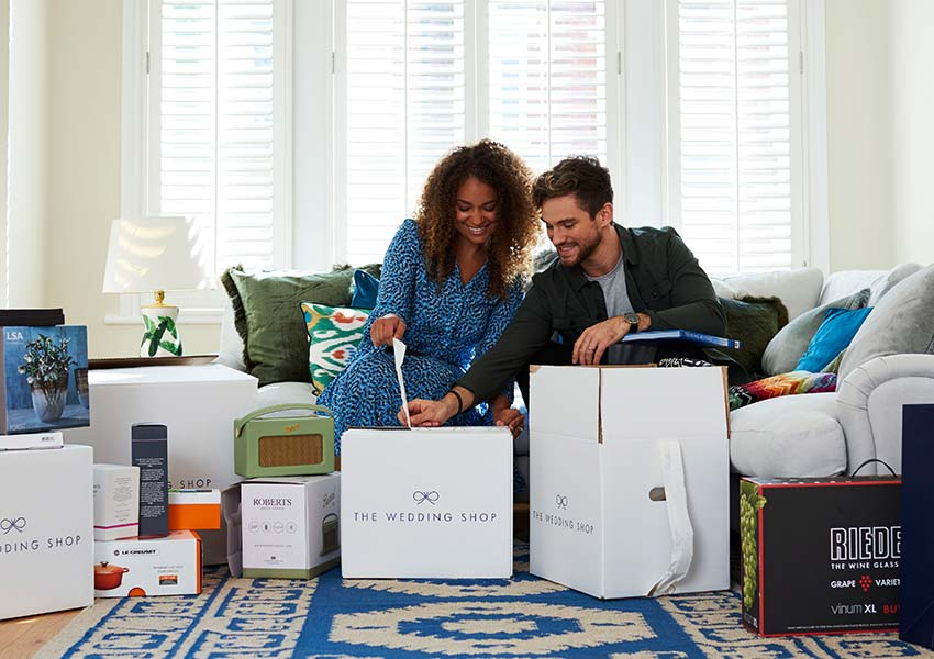 Newly married couple opening wedding gifts from The Wedding Shop