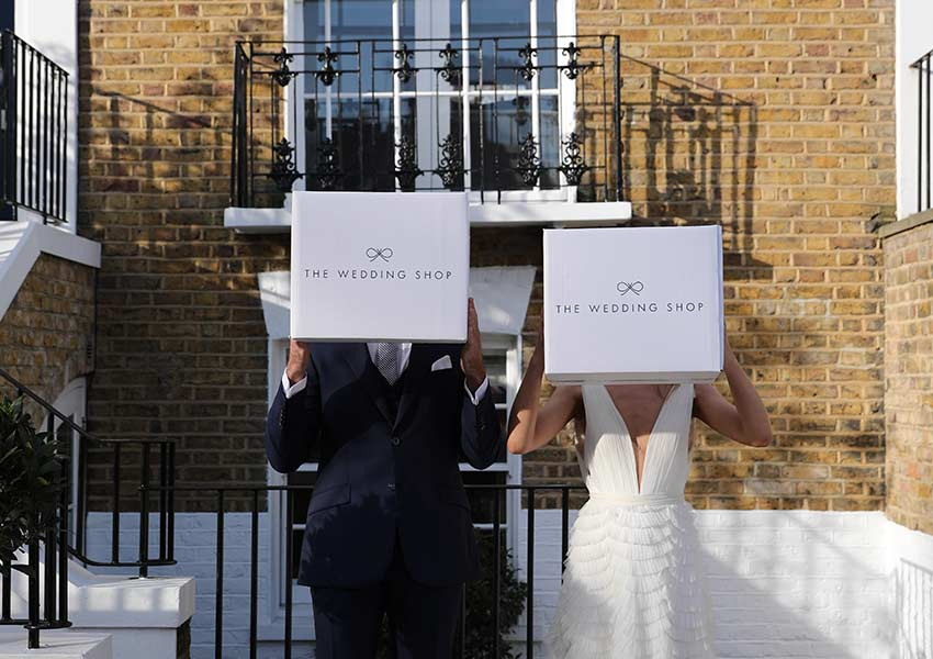 Newly married couple holding wedding gift boxes