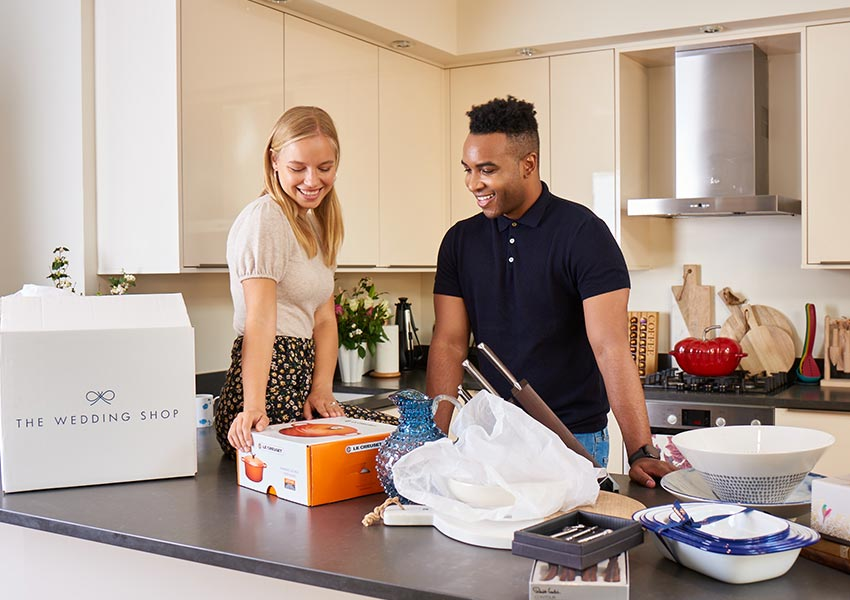 Newly married couple opening wedding gifts in kitchen