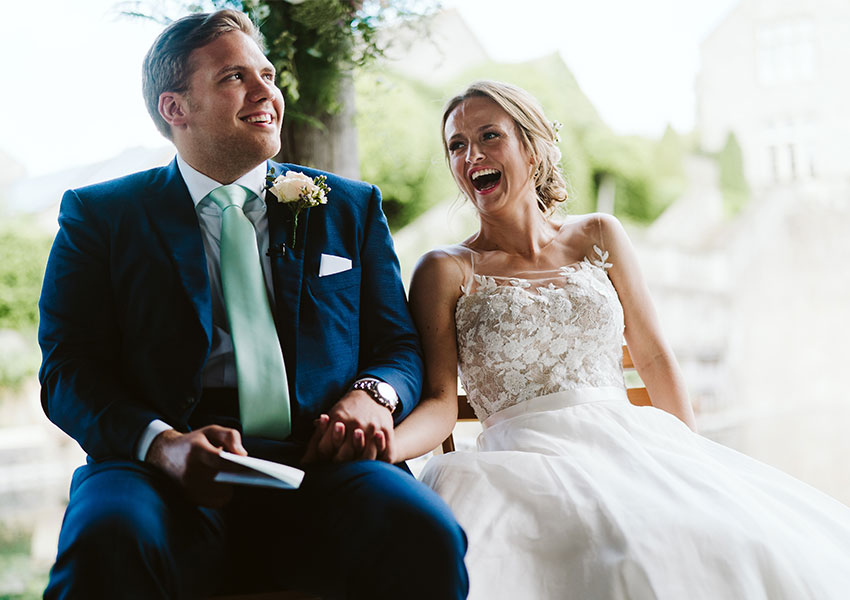 Beautiful newly married couple laughing on their wedding day outside