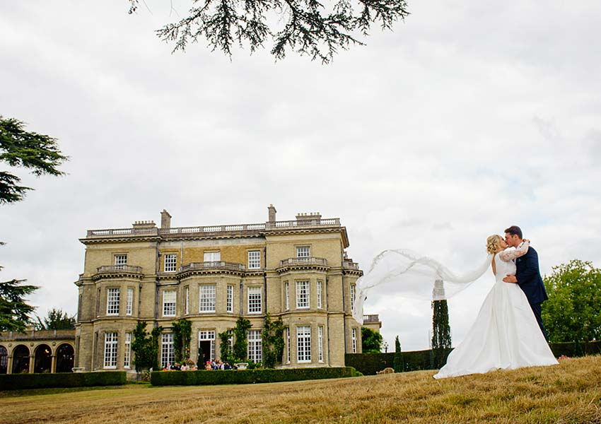 Stunning couple kissing outside hedsor house on their wedding day