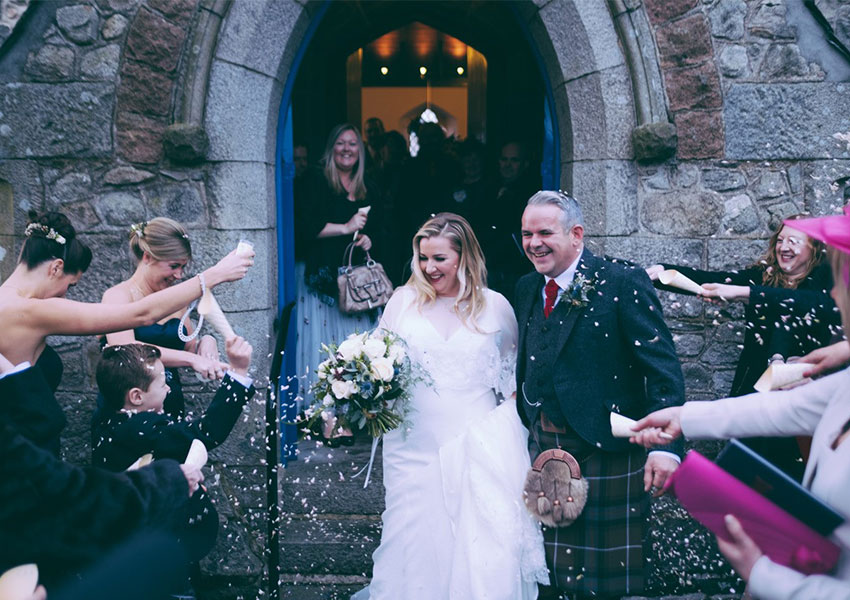 Couple on their wedding day in Scotland being showered with confetti