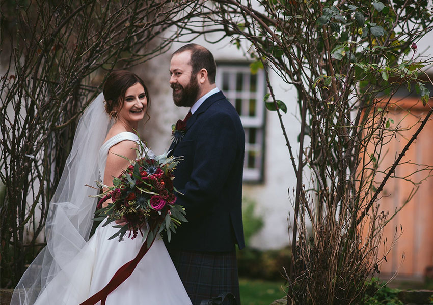 Newly married couple on their wedding day in autumnal cottage garden
